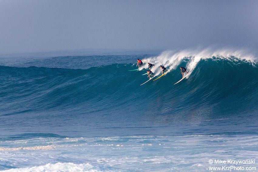 Surfers riding a large wave at Waimea Bay, North Shore, Oahu