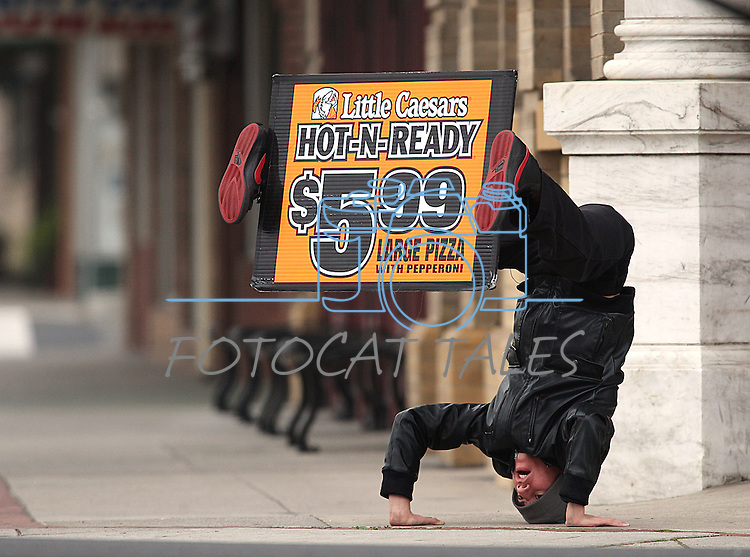 Cris Rod, 19, entertains drivers from a street corner in Oakdale, Ca., near Modesto, on Jan. 16, 2011.<br /> Photo by Cathleen Allison