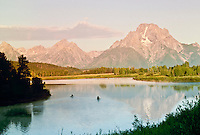 Just before sunrise, canoes in the mist on small lake by Grand Tetons Wyoming