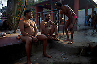 In the spare time between training sessions the pehlwani (traditional Indian wrestlers) gather on the bank of the Gange river to enjoy a chat between friends. . Kolkata, India.