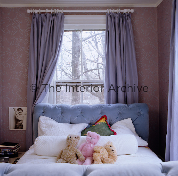 Three teddy bears sit on a sleigh bed in the corner of a pale purple bedroom