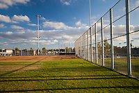 A setting sun casts lovely shadows over the baseball field at Stanton Central Park.  The tall fence frames the field.