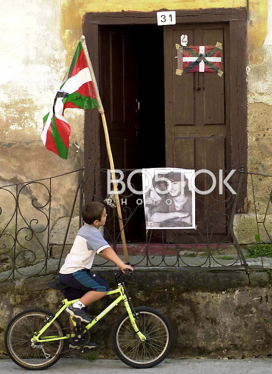 A child observes a picture of dead ETA member Hodei Galarraga on September 25, 2002, in the town of Zaldibia, Basque Country. (Ander Gillenea / Bostok Photo)