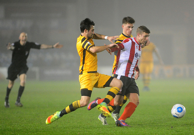 Lincoln City's Jack Muldoon vies for possession with Maidstone United's Tom Mills and Maidstone United's Jack Paxman<br /> <br /> Photographer Andrew Vaughan/CameraSport<br /> <br /> Vanarama National League - Lincoln City v Maidstone - Saturday 26th November 2016 - Sincil Bank - Lincoln<br /> <br /> World Copyright &copy; 2016 CameraSport. All rights reserved. 43 Linden Ave. Countesthorpe. Leicester. England. LE8 5PG - Tel: +44 (0) 116 277 4147 - admin@camerasport.com - www.camerasport.com
