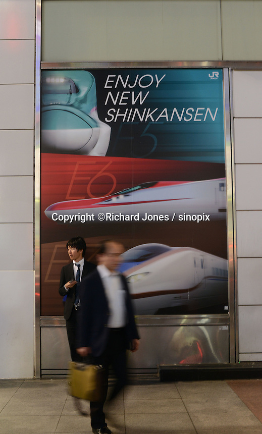 Passengers at Tokyo Station.  Tokyo station is one of big terminal stations in Tokyo.  Various Shinkansen bullet trains depart from Tokyo station.  Businessman is standing and another businessman is passingin front of a big new Shinkansen advert.