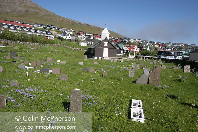 The graveyard and church in the village of Sørvágur on the island of Vágar, close to the Faroe Islands' airport. The Faroes, a group of 18 islands between the Norwegian Sea and the North Atlantic Ocean became an autonomous region of the Kingdom of Denmark in 1948. At the start of the 21st century the population stood at around 50,000 with the economy relying almost entirely on aquaculture and fishing.