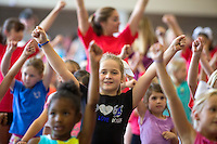 NWA Democrat-Gazette/JASON IVESTER <br /> Addison Crafts, 7, of Rogers follows along on Thursday, Sept. 10, 2015, with other participants in the Mini Mounties Spirit Clinic at Rogers High School. About 200 girls from kindergarten through fifth grade learned cheer and dance routines from the Mounties Spirit Squads.