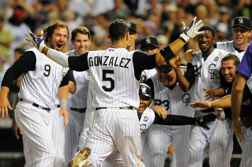 31 JULY 2010: Colorado Rockies center fielder Carlos Gonzalez (5) celebrates with teammates, including Colorado Rockies third baseman Melvin Mora (6) after hitting a walk-off homerun, completing the cycle for Gonzalez during a regular season Major League Baseball game between the Colorado Rockies and the Chicago Cubs at Coors Field in Denver, Colorado.   *****For Editorial Use Only*****