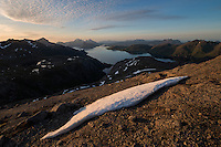 Late summer snow on rocky summit of Hestræva mountain peak, Flakstadøy, Lofoten Islands, Norway