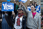 Women holding 'Yes' signs at a pro-independence gathering in George Square, Glasgow. The gathering brought together Yes Scotland supporters who favour Scotland leaving the union with the United Kingdom. On the 18th of September 2014, the people of Scotland voted in a referendum to decide whether the country's union with England should continue or Scotland should become an independent nation once again and leave the United Kingdom.