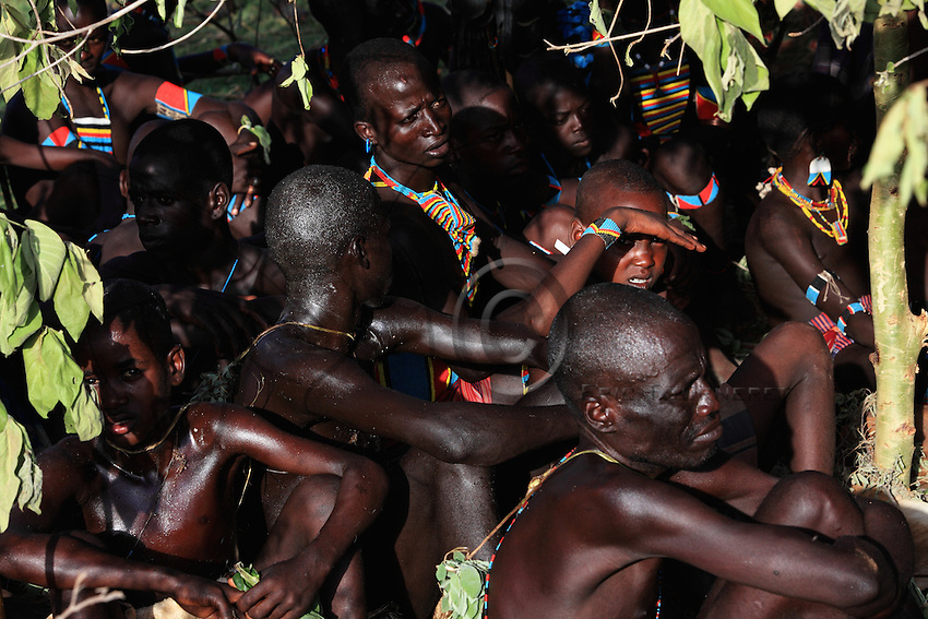 The village of Bori, in the land of the Banas during the initiation of the young Aïke. Under the leave-covered shelters, the chokolés and the mazas wait while sipping whey and coffee.///Village de Bori, pays Bana pendant l'initiation du jeune Aïké. Sous des abris recouverts de feuillages, les chokolés et les mazas attendent assis en dégustant lait caillé et café.