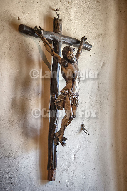 Crucifix and cross hanging on a wall at the Carmel Basilica and Mission, spring, Carmel, Calif.