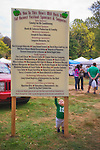 Mill Neck, New York, U.S. 12th October 2013. A toddler boy reaches up to touch the information sign listing sponsors, supporters, and vendors at the entrance to the annual Fall Harvest Festival, also known as Apple Fest, which attracts tens of thousands of visitors, on the grounds of Mill Neck Manor, an historic Gold Coast estate, during Columbus Day weekend. Proceeds benefit the Mill Neck Family of organizations including the Mill Neck Manor School for the Deaf.