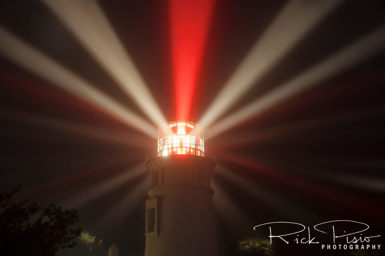 The Umpqua River Lighthouse at the entrance to Winchester Bay along the Oregon coast. The lamp was lit for the first time on December 31, 1894, with a signature of two white flashes followed by a red flash. <br /> The 65 foot tower is brick overlaid with cement plaster stands 165 feet above sea level, is five feet thick at the base and tapers to 21 inches thick at the parapet.