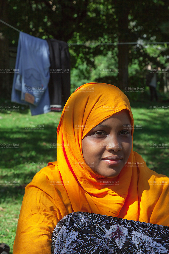 Italy. Lombardy Region. Como. Dega is 18 years old and comes from Somalia. She is an homeless african migrant living in the park below the San Giovanni railway station. She covers her hair under a colorful orange hijab. A hijab is a veil that covers the head and chest, which is particularly worn by some Muslim women in the presence of adult males outside of their immediate family. 12.08.2016 © 2016 Didier Ruef
