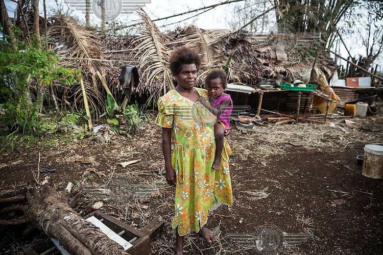 Margaret Amon (about 40) with her two year old daughter Ester near their house in Etas village. On 13 March 2015 Margaret's house was badly damaged by Cyclone Pam and now she and her family lives in a tent.
