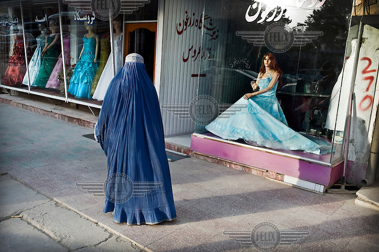 A woman in full burqa walks past a shop selling wedding dresses. The dresses for sale are in stark contrast to the traditional clothing worn by most women on the streets of Kabul.