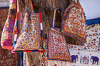 Decorated handbags on sale hanging from tree in street market in City Palace Road, Udaipur, Rajasthan, Western India