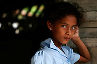 Maria Mercedes Louis Cardenas, 7, stands at the door of her grandmother's kitchen in El Trepiche, Nicaragua, on Wednesday, June 28, 2006. Cardenas is in second grade and a third generation Baha'i. (Photo by Bryce Yukio Adolphson/Brooks Institute of Photography, © 2006)