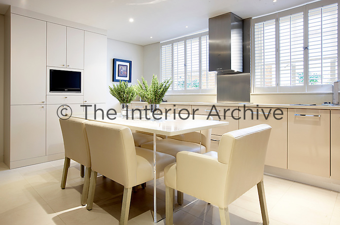 Comfortable leather upholstered chairs surround the table in this modern and sleek kitchen