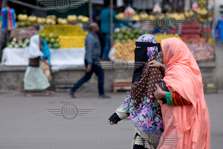 A woman in a niqab passes a stall selling fruit and vegetables for sale in a city market.