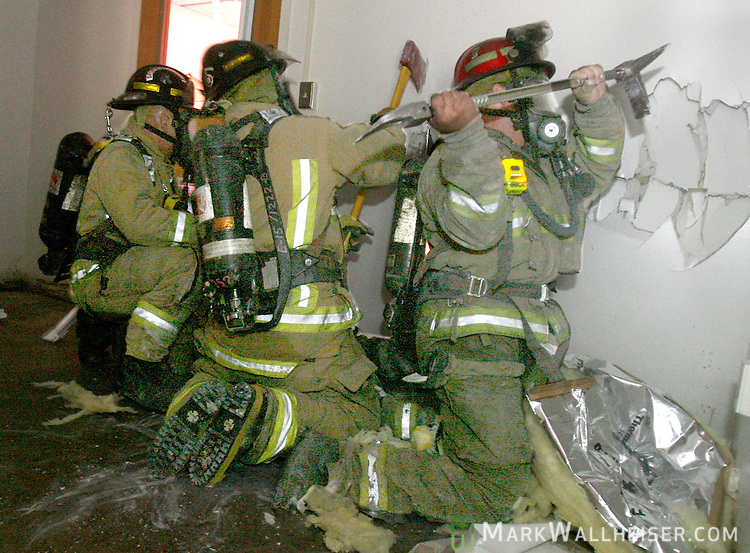 Three firefighters from Tallahassee Fire Department Engine 15 chop and smash their way through a wall in the old FSU Prefessional Development building to survive after the roof collapsed during Tallahassee Fire Department's safety and survival training, firefighters break through the walls in and effort to find their way out of a commercial building fire alive after a roof collapse in Tallahassee, Florida June 8, 2007.    (Mark Wallheiser/TallahasseeStock.com)