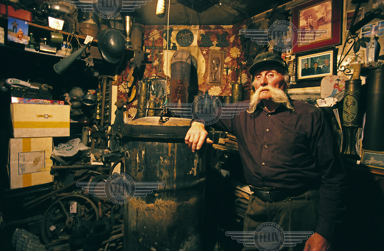 74 year old Eugene 'Bill' Van Oudendyke stands in his house surrounded by metal objects such as wheels, ammunition canisters and helmets.  He is a steel worker who collects scrap iron from remnants of the world wars to display in his house. .
