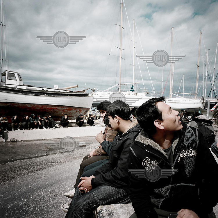 Afghan refugees wait in the harbour on the main road for trucks that go to the port, to try to hide in one of them. Patras is home to about 3,000 illegal immigrants. Most of them are Afghans, although there are also some Iranians and Uzbeks. They stop in Patras to try and find passage to various European destinations by hiding in ships, containers and trucks parked in the port. If they are lucky they will make it to their destination. Many of them live in shacks made from cartons, plastic and wood they found on the beach. To shelter from the cold they also squat in abandoned buildings, living without water and electricity. The living conditions are inhumane and unhygienic.