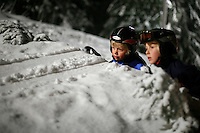 Two boys check the ski jumping track in the Schroderbakken, near the famous ski jumping arena Holmenkollen, Oslo, Norway.