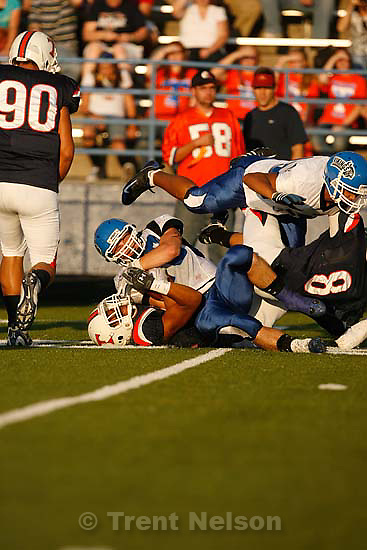 Provo - Timpview's Ofa Latu (bottom) tries to rip the ball from PG's Kyle Tucker. Timpview vs. Pleasant Grove high school football Friday, August 21 2009...