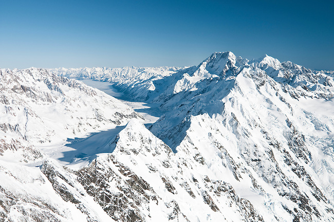 Stunning views from the summit of the Mt. Elie de Beaumont 3109m along the ridge of the Main Divide with highest New Zealand peaks on right- Mt. Cook 3754m and Mt. Tasman 3497m. Tasman Glacier to the left and Mt. Cook Village under the local clouds further on the left - Mt. Cook National Park, Mackenzie Country