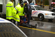 "December 7, 2011  (Washington, DC)  Officers of the DC Metropolitan Police arrest a man after he laid down and blocked a busy downtown street with other OccupyDC protesters. The arrests came after the OccupyDC group and protesters from ""Our DC"", a group backed by a powerful union, failed to come together in solidarity, each occupying separate ends of a block on K street. An estimated four dozen protesters were arrested.   (Photo by Don Baxter/Media Images International)"