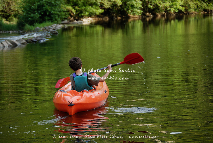 Boy (12-13) kayaking in river
