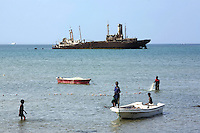 Somaliland. Sahil province. Berbera. Red sea on the gulf of Aden. Ship's wreck near the coast. Ship aground. Stranded merchant vessel. A fisherman is using fishing nets. A group of black muslim boys are enjoying a bath in the water. Somaliland is an unrecognized de facto sovereign state located in the Horn of Africa.  © 2006 Didier Ruef
