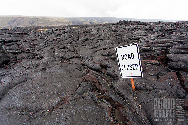 """Road Closed"" sign emerging from lava field, Hawai'i Volcanoes National Park, Big Island."