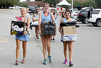 NWA Democrat-Gazette/DAVID GOTTSCHALK  Elle Henson (from left), Caroline Baughn and Genesis Moncada, sophomores at the University of Arkansas and  volunteers with Panhellenic Recruitment 2017, help move items Thursday, August 10, 2017, into campus housing in Fayetteville. Students, including those in the University band and participating in sorority recruitment, had the opportunity to move in early.