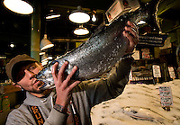 A worker holds up a salmon at Pike Place Market in Seattle Washington.