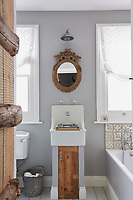The bathroom is decorated in soft grey with white bathroom fittings. A wash basin is set on a pedestal unit with a rustic wooden door.