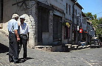 Men talking at the Qafe or Neck of the Bazaar, a busy intersection of 5 streets that forms the heart of the old town of Gjirokastra, Southern Albania. Most of the Ottoman houses date from the 17th and 18th centuries. Gjirokastra was settled by the Greek Chaonians, the Romans and Byzantines before becoming an Ottoman city in 1417. Its old town was listed as a UNESCO World Heritage Site in 2005. Picture by Manuel Cohen