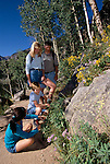 A family of four share nature by examining wildflowers along a trail in Rocky Mtn Nat'l Park, CO.