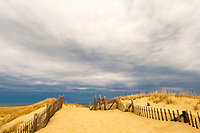 The path leads through the sand dunes to the coast of the Cape Cod National Seashore under overcast blue-gray sky.