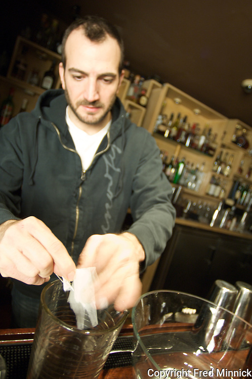 The Drawing Room's chief mixologist Charles Joly opens a pouch of chai tea for his tea punch called the Guild Meeting.