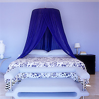 In this cool and refreshing bedroom an ultramarine bed canopy hangs above a blue and white floral bedcover