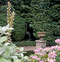 A sculpture of a heron is concealed in the shrubbery in the garden