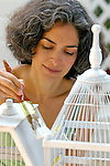 Mature woman painting bird cage