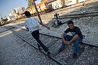 Grecia, Patrasso 2011: rifugiati afghani in un improvvisato campo in una stazione ferroviaria abbandonata. Un ragazzo è seduto sorridente sui binari. Un'altro cammina lungo i binari. Grece ville de Patras  2011 - refugies afghans dans une gare abandonnee