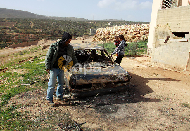 A Palestinian man inspects the wreckage of his car in the village of Majdal Bani Fadel, near the West Bank City of Nablus, 20 December 2012. According to Palestinian security officials two cars were set on fire in a raid by Jewish settlers. Photo by Nedal Eshtayah