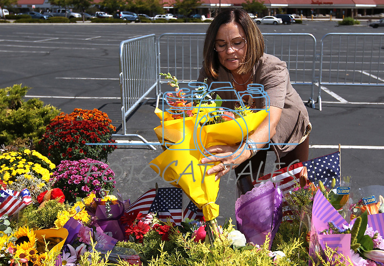 Judy Minetto leaves flowers at the memorial outside the IHOP in Carson City, Nev., on Friday, Sept. 8, 2011. The investigation continues into the Tuesday shooting that ended with five people dead, including the gunman, and seven wounded. (AP Photo/Cathleen Allison)