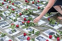 """Am Sonntag den 22. Juli 2018 fand in Berlin auf Initiative der Jugendorganisation """"Falken"""" vor der norwegischen Botschaft ein Gedenken an die Opfer des Massakers von Utoeya und Oslo statt. Der norwegische Rechtsextremist hatte am 22. Juli 2011 in Oslo mit einer Autobombe vor dem Parlament acht Menschen getoetet und anschliessen, als Polizist verkleidet, auf der Insel Utoeya 69 Jugendliche ermordet. Auf Utoeya fand ein Ferienlager der sozialistischen Jugendorganisation """"AUF"""" statt.<br /> Vor der Botschaft wurden Portraits der 77 Opfer ausgelegt.<br /> Im Bild: Menschen legen Rosen auf die Portraits.<br /> 22.7.2018, Berlin<br /> Copyright: Christian-Ditsch.de<br /> [Inhaltsveraendernde Manipulation des Fotos nur nach ausdruecklicher Genehmigung des Fotografen. Vereinbarungen ueber Abtretung von Persoenlichkeitsrechten/Model Release der abgebildeten Person/Personen liegen nicht vor. NO MODEL RELEASE! Nur fuer Redaktionelle Zwecke. Don't publish without copyright Christian-Ditsch.de, Veroeffentlichung nur mit Fotografennennung, sowie gegen Honorar, MwSt. und Beleg. Konto: I N G - D i B a, IBAN DE58500105175400192269, BIC INGDDEFFXXX, Kontakt: post@christian-ditsch.de<br /> Bei der Bearbeitung der Dateiinformationen darf die Urheberkennzeichnung in den EXIF- und  IPTC-Daten nicht entfernt werden, diese sind in digitalen Medien nach §95c UrhG rechtlich geschuetzt. Der Urhebervermerk wird gemaess §13 UrhG verlangt.]"""