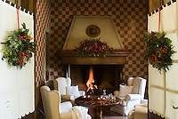 Festive Christmas wreaths hang on the double doors that open into the cosy living room with a roaring fire and hand-painted checked walls